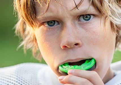 Teen boy placing athletic mouthguard