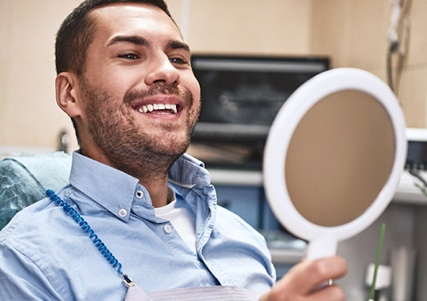 Man in blue looking at his smile in the mirror