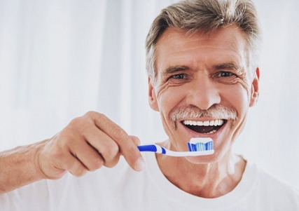 older man about to brush teeth