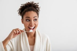 Woman brushing her teeth looking away from camera