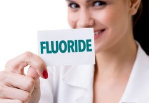 Dentist in Saginaw holding a fluoride card.