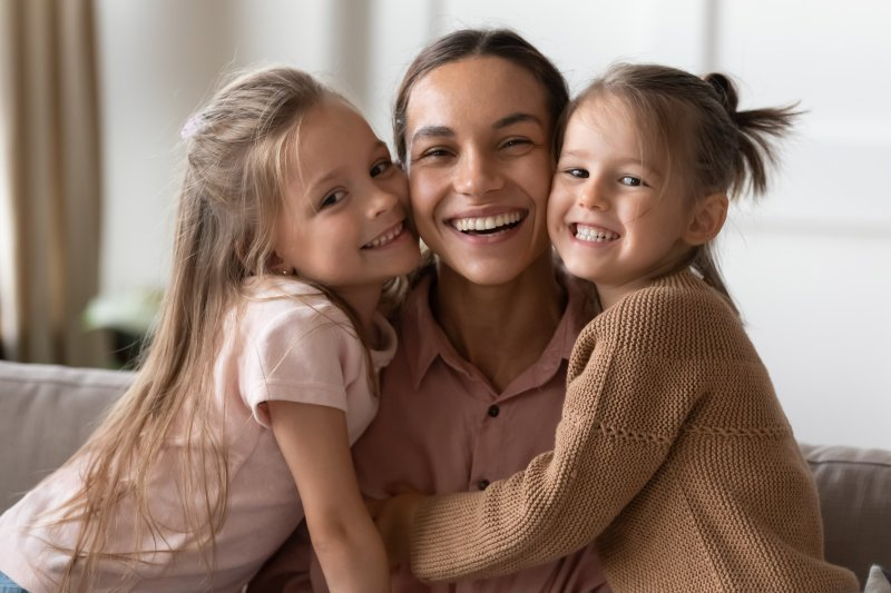 Mom smiling with two daughters
